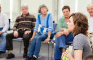 Adults sitting in a group listening to one woman speak